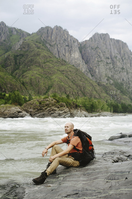 Side view of male hiker with backpack sitting on rocks at riverbank against mountain