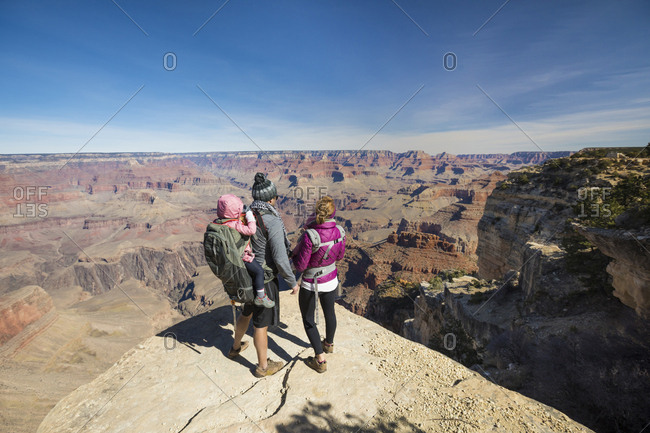Parents with children standing on mountain against blue sky during sunny day at Grand Canyon National Park