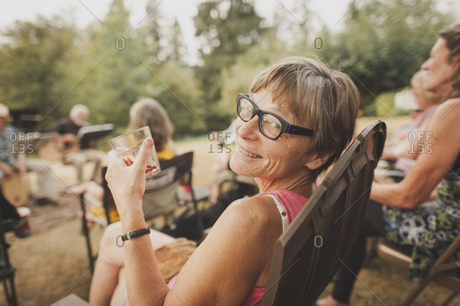 Portrait of smiling woman having drink while sitting on chair in yard