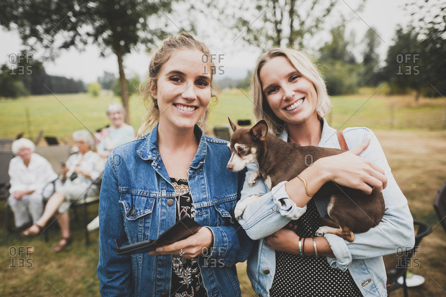 Portrait of friends with Chihuahua standing in yard