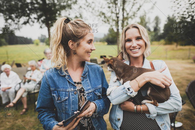 Portrait of woman holding Chihuahua while standing with friend in yard