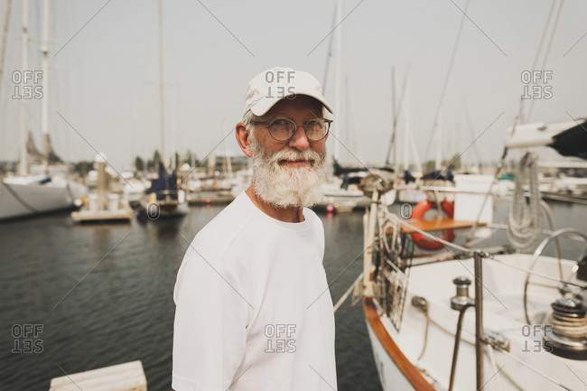 Portrait of senior man standing at harbor against clear sky