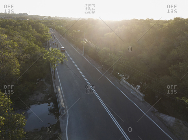 High angle view of road amidst trees against sky during sunset