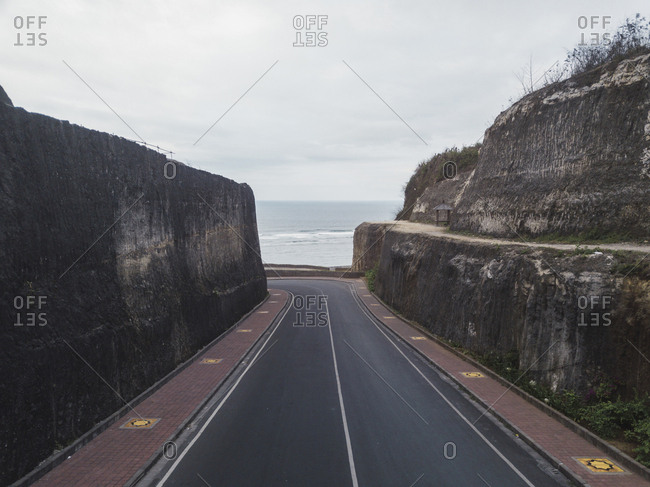 Diminishing perspective of road amidst surrounding walls by sea against sky at Bali