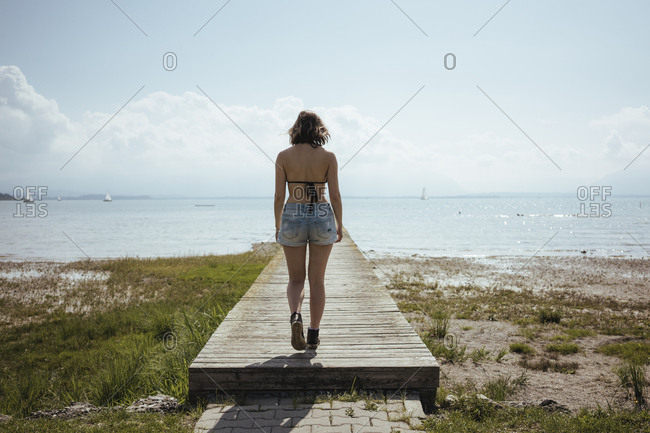 Rear view of woman in bikini walking on pier towards lake against sky during sunny day