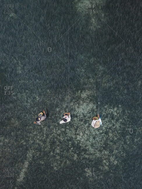 High angle view of male friends fishing while standing in sea
