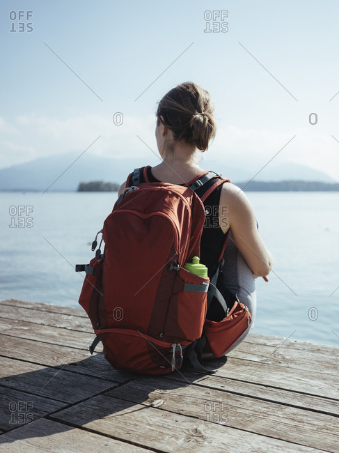 Rear view of woman with backpack looking at lake while sitting on pier against sky during sunny day