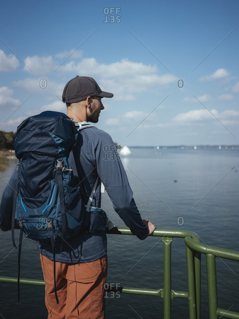Rear view of man with backpack looking at lake while standing against sky during sunny day