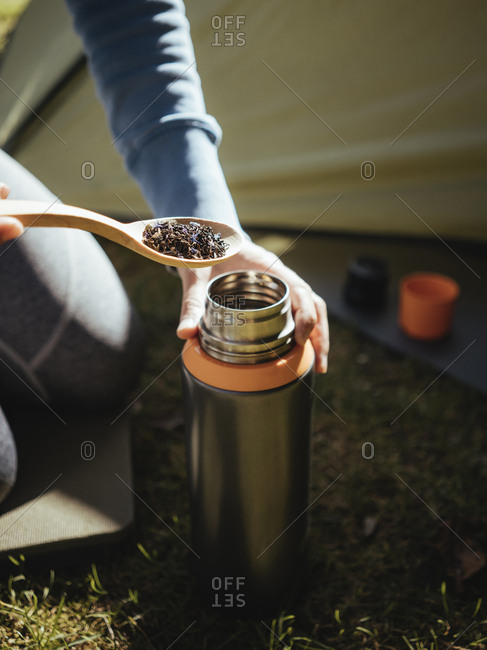 Midsection of woman making drink while kneeling at campsite