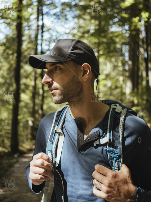 Male hiker with backpack looking away while standing in forest