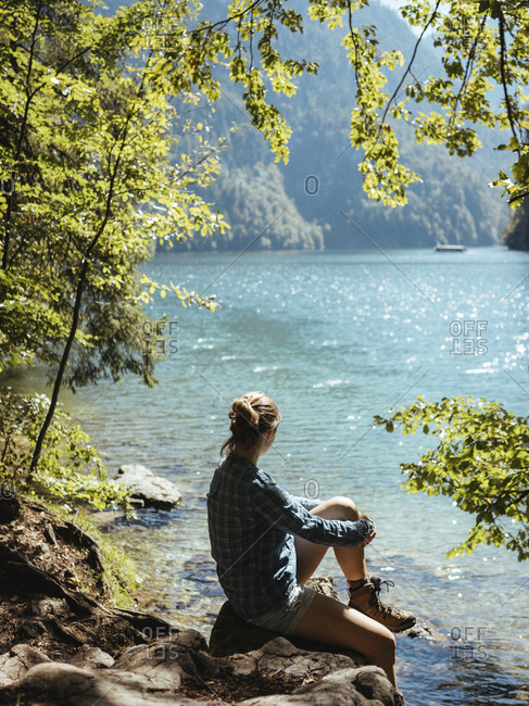 Side view of woman looking at lake while sitting on rocks in forest during sunny day