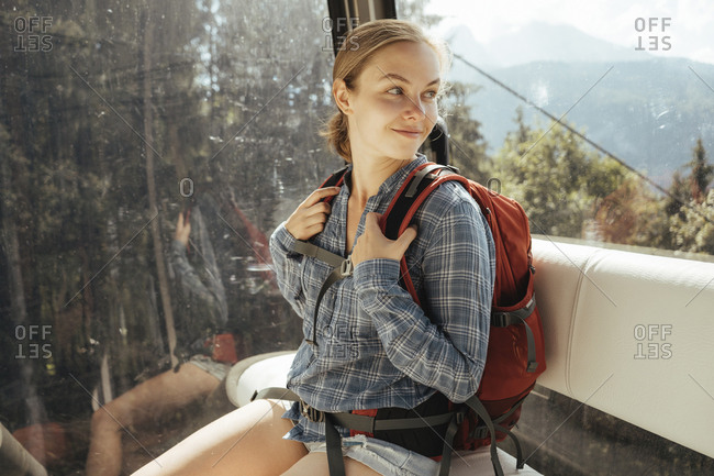 Smiling woman looking through window while traveling in overhead cable car
