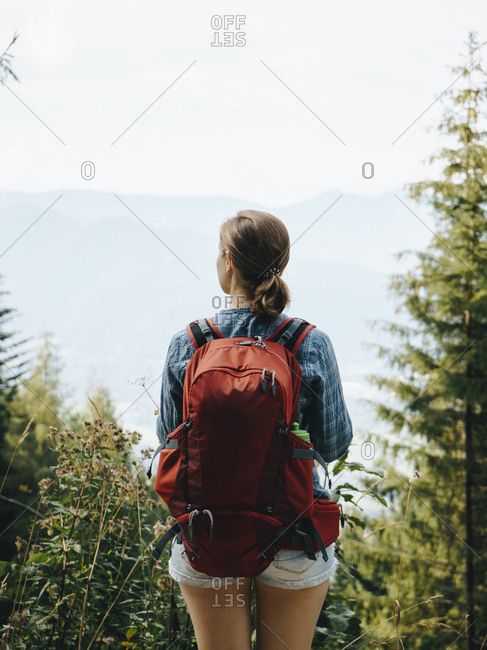Rear view of female hiker with backpack standing against sky in forest