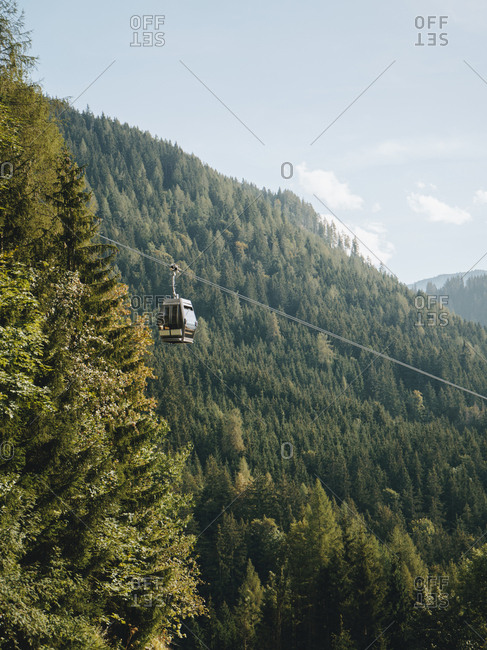 Overhead cable car moving over mountain against sky during sunny day