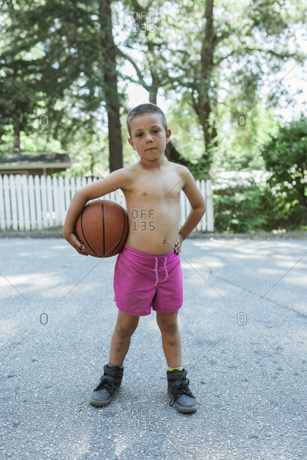 Portrait of shirtless boy holding basketball while standing on footpath against trees at park