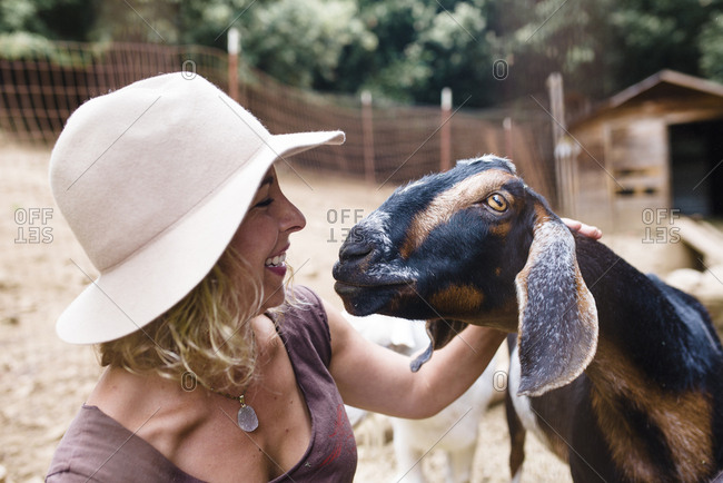 Close-up of smiling woman wearing hat looking at goat in farm