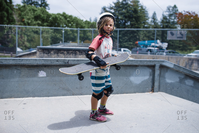 Portrait of girl holding skateboard while standing on sports ramp at park