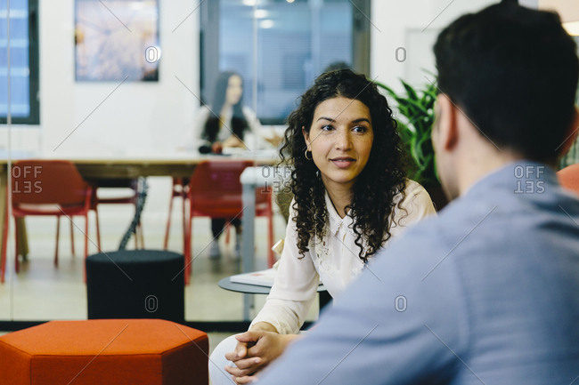 Businessman discussing with female colleague while sitting in creative office