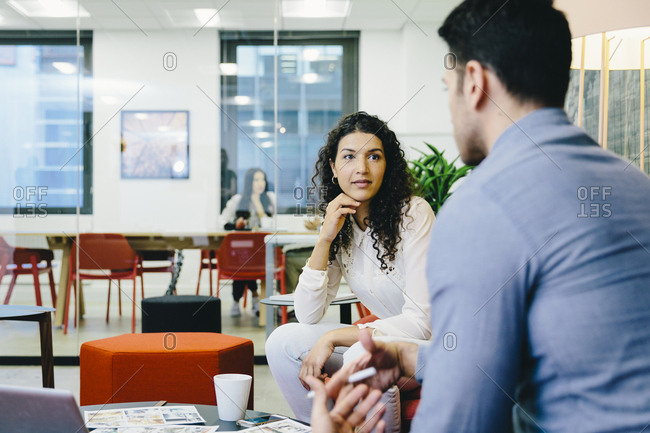 Side view of businessman discussing with female colleague while sitting in creative office