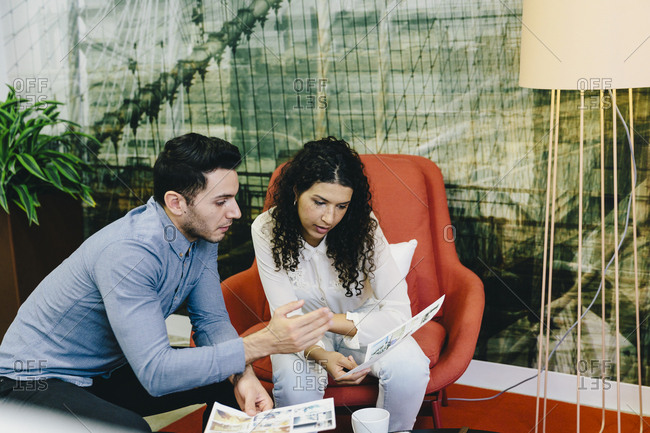 Colleagues discussing photograph printouts while sitting in creative office