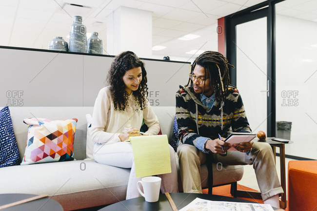 Businesswoman explaining to male colleague over diary while sitting on sofa in creative office
