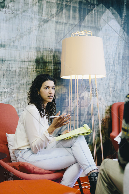 Businesswoman discussing with male coworker while sitting in creative office