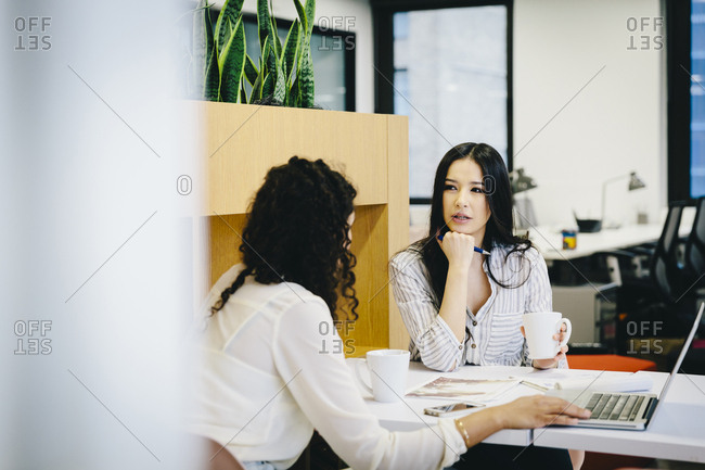 Female entrepreneurs planning over laptop computer while sitting at desk in office