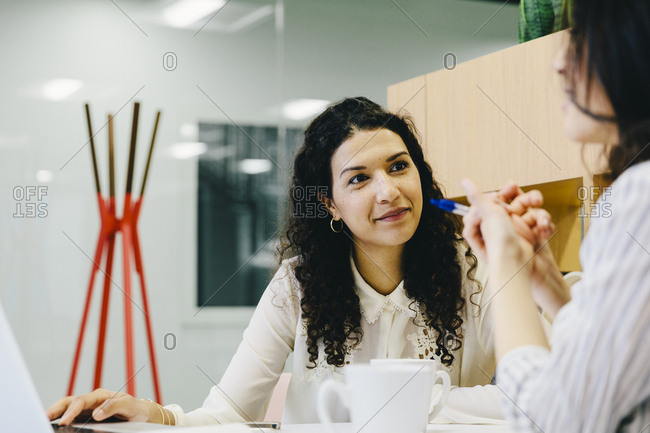 Female entrepreneurs discussing while sitting at desk in office