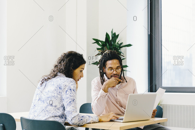 Businesswoman discussing data over laptop computer with businessman in office
