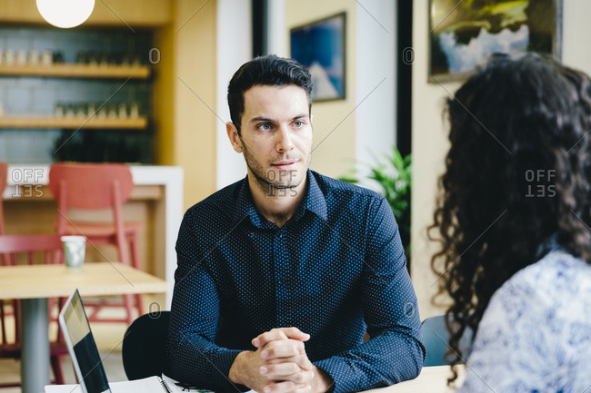 Colleagues discussing business plan while sitting at desk in office