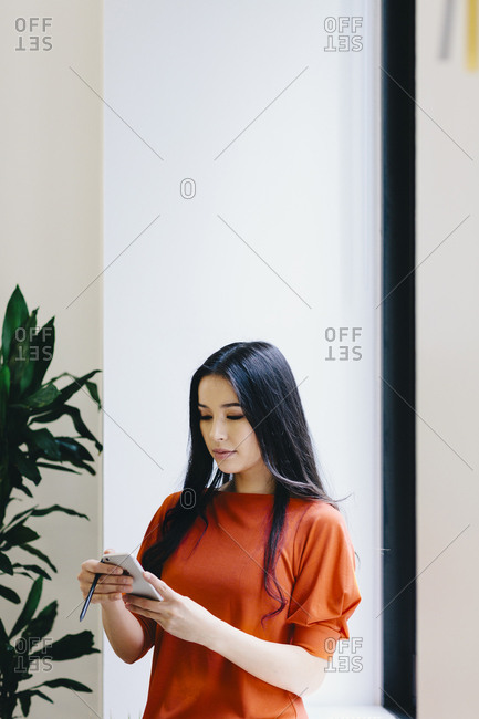 Businesswoman using smart phone while standing against wall in office