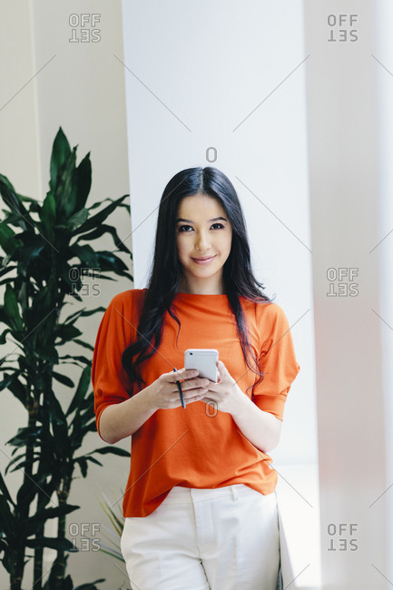 Portrait of businesswoman using smart phone while standing against wall in office