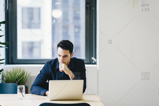 Businessman using laptop computer on desk while sitting in office