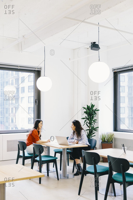 Female colleagues brainstorming while sitting at desk in office