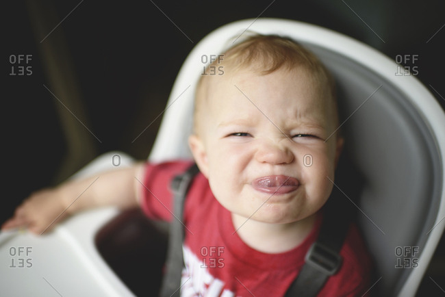 High angle portrait of cute baby girl sticking out tongue while sitting on high chair at home