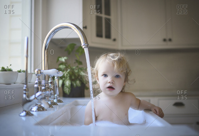 Portrait of cute shirtless girl bathing in sink at home