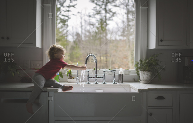 Side view of cute girl washing hand in sink while sitting on kitchen counter against window at home