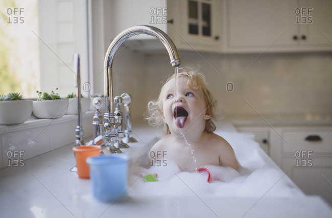 Cute shirtless girl drinking water from faucet while bathing in sink at home