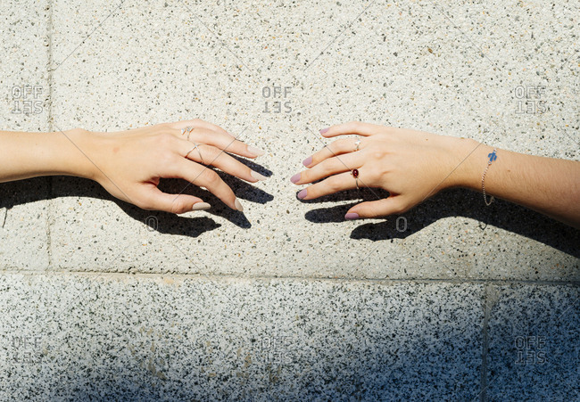 Cropped image of friends wearing jewelries against wall during sunny day
