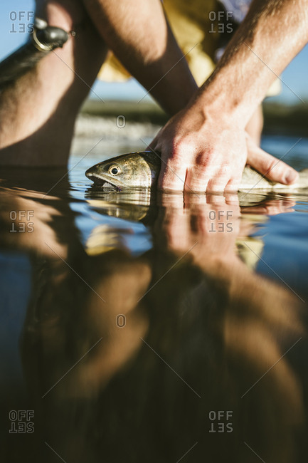 Mid section of man holding fish while standing in lake