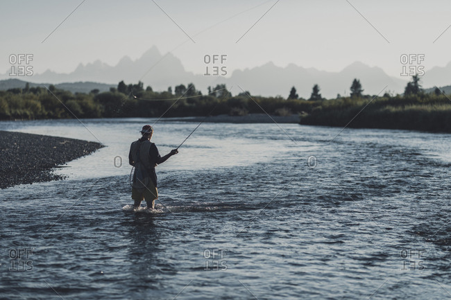 Rear view of man fishing while standing in lake against clear sky during sunset