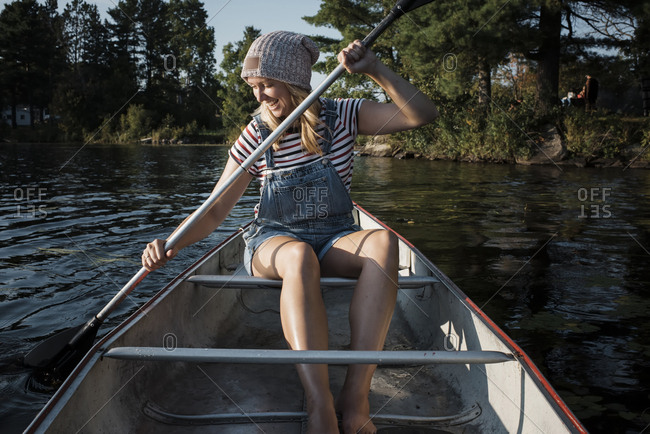 Happy woman rowing boat on lake at Algonquin Provincial Park