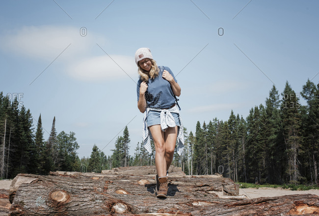 Low angle view of smiling woman walking on logs against sky in forest during sunny day