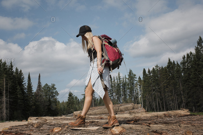 Side view of woman with backpack walking on logs against cloudy sky in forest during sunny day