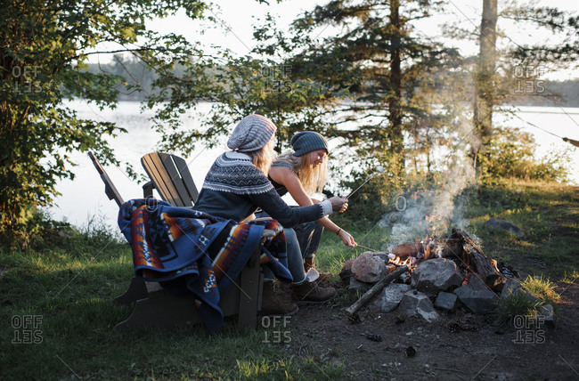 Female friends cooking marshmallows over campfire while sitting on chairs in forest