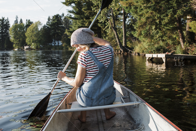 Rear view of woman rowing boat on river against trees in forest