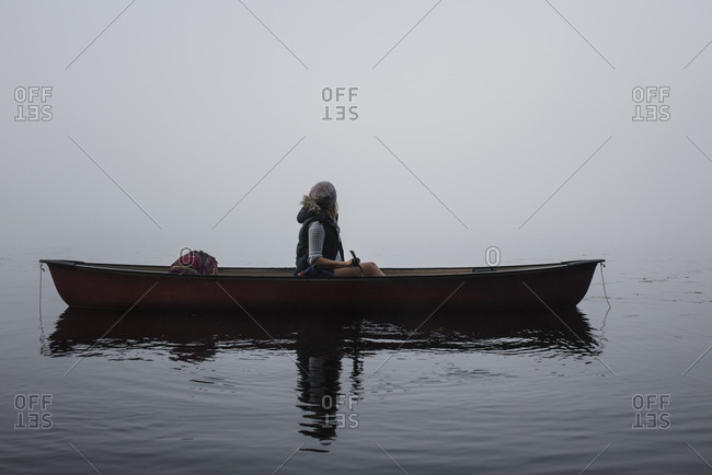 Woman sitting in boat on river at Algonquin Provincial Park during foggy weather