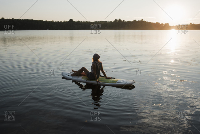Side view of woman sitting on paddleboard on river against sky during sunset
