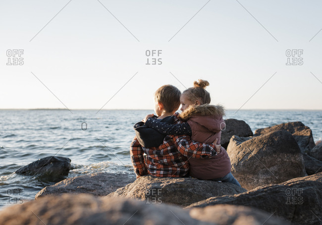 Rear view of siblings sitting on rocks at lakeshore against clear sky during sunset