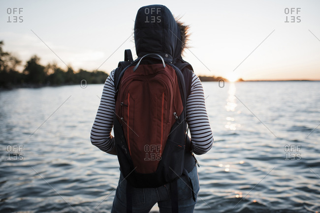 Rear view of woman with backpack standing at lakeshore against clear sky during sunset